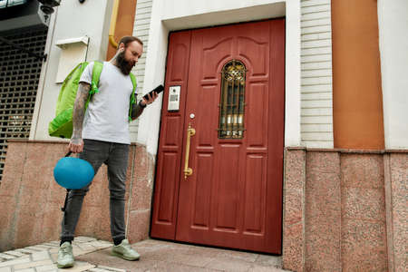Full length shot of bearded delivery man with thermo backpack using smartphone, standing by the door, while completing the order. Courier, delivery service concept
