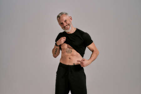 Be a motivation. Smiling middle aged muscular man lifting black t shirt showing, pointing at his abs, tattoos while posing in studio over grey background