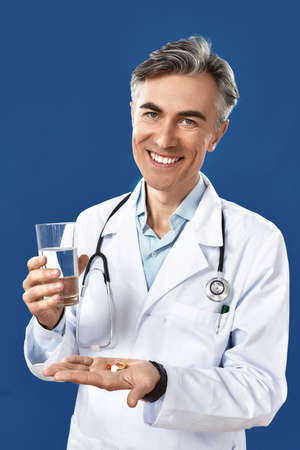 Cheerful mature male doctor in medical uniform giving pills and glass of water, smiling at camera while standing against blue navy background Фото со стока