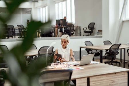 Smart girl. Young tattooed business woman with short haircut using digital tablet while sitting at her workplace in the modern office 免版税图像