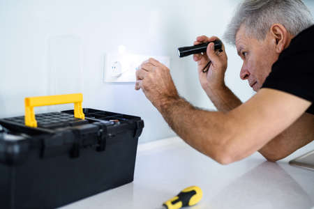 Aged electrician, repairman in uniform working, examining socket in the kitchen using flashlight. Repair service concept