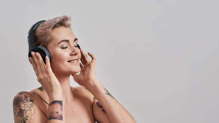 Clear Sound. Attractive tattooed woman with pierced nose and short hair in headphones enjoying listening to music isolated over grey background