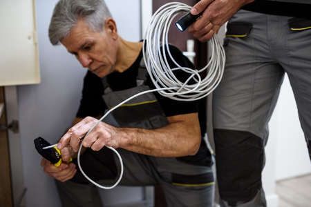 Fix it. Cropped shot of aged electrician, repairman in uniform working, examining cable, checking voltage in fuse box using multimeter while his colleague holding cable