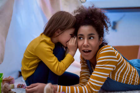 Listening is a key. African american woman baby sitter entertaining caucasian cute little girl. They are gossiping and telling secrets sitting in kids room. Leisure activities, babysitting concept