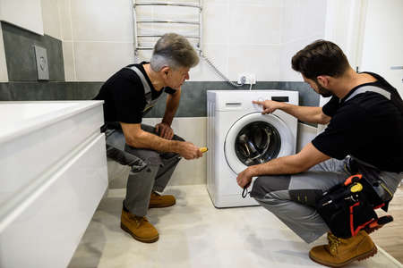 Full length shot of two repairmen, workers in uniform working, reading washing symboles on washing mashine before fixing it, holding screwdriver indoors. Repair service concept