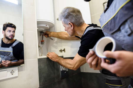 Affordable repairing. Aged plumber, repairman in uniform fixing electric boiler with wrench while his young colleague helping him, holding sticky duct tape indoors. Repair service concept Stock fotó