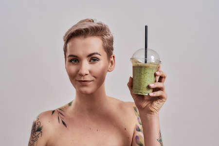 Choose Green. Attractive tattooed woman with pierced nose and short hair looking at camera, while holding green detox smoothie isolated over grey background