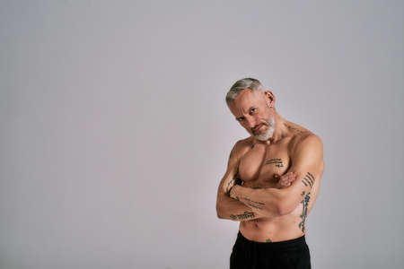 Half naked middle aged muscular man looking at camera, showing his body, while posing in studio over grey background Stock Photo