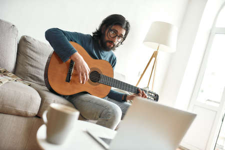 Watching video tutorial. Young man sitting on sofa at home and learning guitar online. Sitting on sofa at home and looking at laptop