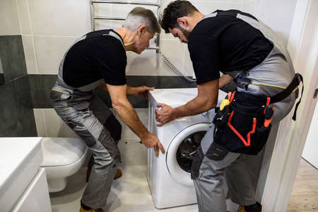 Always there for you. Two repairmen, workers in uniform working, moving washing mashine for fixing it, holding screwdriver in the bathroom. Repair service concept