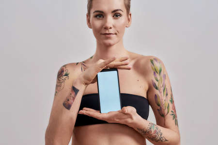 All that you need. Attractive tattooed woman with pierced nose and short hair advertising app, holding smartphone with blank screen isolated over grey background Stock Photo