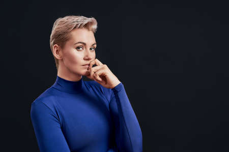 Portrait of attractive woman with pierced nose and short hair in blue turtleneck looking thoughtful at camera, holding finger on her mouth isolated over dark background