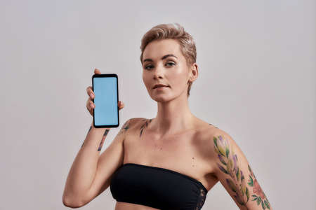 New App. Attractive tattooed woman with pierced nose and short hair advertising app, holding smartphone with blank screen isolated over grey background