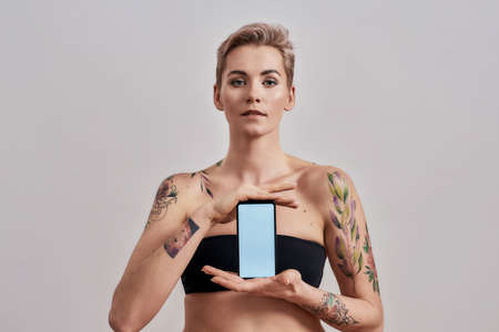 Attractive tattooed woman with pierced nose and short hair advertising app, holding smartphone with blank screen isolated over grey background