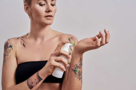Cropped portrait of beautiful tattooed woman with pierced nose and short hair holding plastic bottle with skin care product, body lotion, applying it on hand isolated over grey background 免版税图像