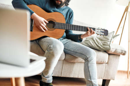 Online lesson. Cropped shot of a young man playing guitar while sittting at home and watching video tutorial on laptop online