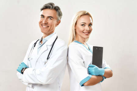 Succesful medical team. Two cheerful doctors, man and woman in medical uniform keeping arms crossed, looking at camera and smiling