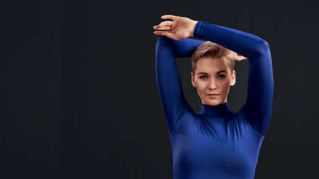 Portrait of attractive woman with pierced nose and short hair in blue turtleneck looking at camera, holding arms above her head isolated over dark background