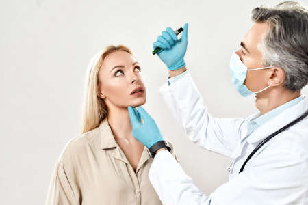 Professional mature male ophthalmologist in medical uniform examining eyes of young female patient while standing against grey background