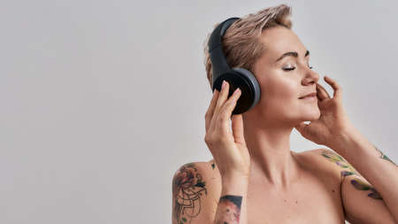 New Sound. Attractive tattooed woman with pierced nose and short hair in headphones enjoying listening to music isolated over grey background