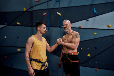 Middle aged man and young male instructor shaking hands, arm wrestling style, standing against climbing wall. Concept of sport life