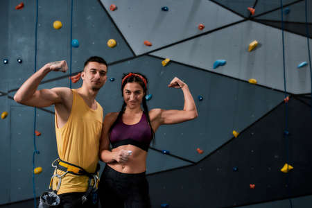 Young male instructor and woman looking at camera, showing biceps, standing against artificial training climbing wall 免版税图像