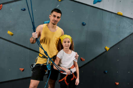 Young male instructor and active girl in safety equipment looking at camera, standing against artificial training climbing wall. Concept of sport life and rock climbing 免版税图像