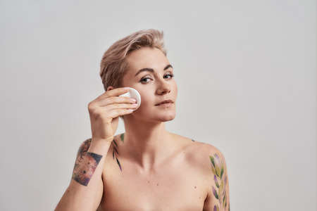 Clear it up. Portrait of beautiful tattooed woman with pierced nose and short hair removing makeup, cleaning skin using cotton pad isolated on grey background Standard-Bild