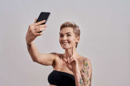 Communication. Attractive tattooed woman with short hair smiling, showing peace sign, taking picture of herself, selfie using smartphone isolated over grey background Stock Photo