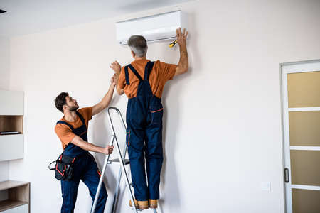 Two workers in uniform, air conditioning masters using ladder while installing a new air conditioner in the apartment. Construction, maintenance and repair concept Stock Photo