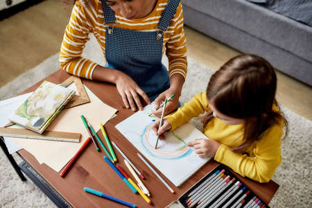Education and Care. Caucasian little girl spending time with african american baby sitter. They are drawing a mouse together
