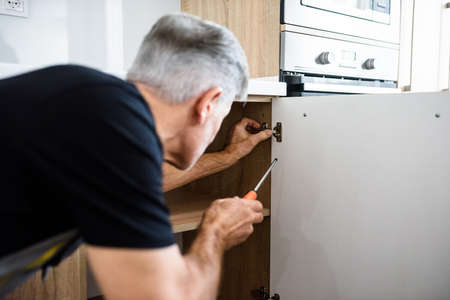 Close up shot of aged repairman in uniform working, fixing kitchen cabinet using screwdriver. Repair service concept