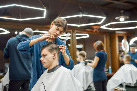 Side view of professional barber girl or female hair stylist making trendy haircut for young handsome caucasian man visiting barbershop