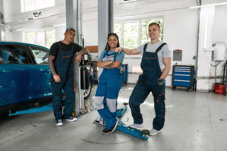 Auto care is our business. Team of proud diverse mechanics in uniform, two men and a woman smiling at camera, while standing at auto repair shop