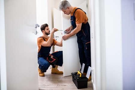 Full length shot of two locksmith, repairmen, workers in uniform installing, working with house door lock using screwdriver. Repair, door lock service concept