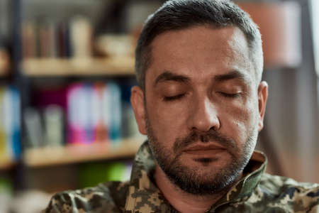 Portrait of middle aged sad, desperate military man sitting with closed eyes during therapy session. Soldier suffering from depression, psychological trauma. PTSD concept