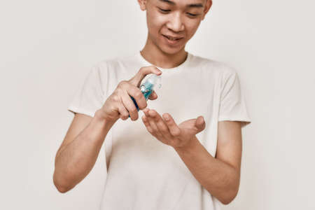 Protect your health. Cropped portrait of young asian man with clean shaven face holding hand sanitizer, applying it on his hands isolated over white background. Health care concept