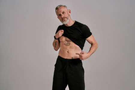 Middle aged muscular man lifting black t shirt showing, pointing at his abs, tattoos while posing in studio over grey background