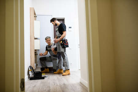 Full length shot of aged electrician, repairman in uniform working, installing ethernet cable or router in fuse box while his young colleague bringing cable Banque d'images