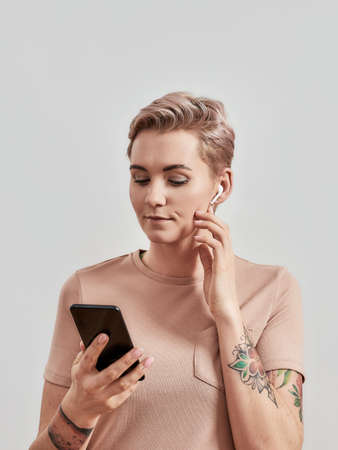 Portrait of tattooed woman with pierced nose and short hair in wireless earbuds or earphones using smartphone isolated over light background