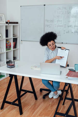 Young afro american woman sitting at her workplace at home and teaching English online, explaining rules of English grammar