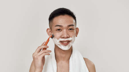 Shave easily. Portrait of shirtless young asian man with towel around his neck shaving his face, looking at camera isolated over white background. Beauty, skincare, morning routine concept