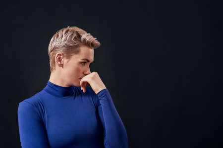 Portrait of attractive woman with pierced nose and short hair in blue turtleneck looking thoughtful, covering mouth with hand isolated over dark background