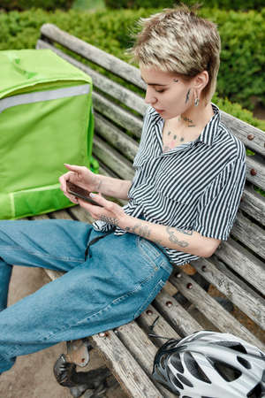 Young delivery woman with thermo bag or backpack checking order using smartphone, sitting on the bench outdoors. Courier, delivery service concept