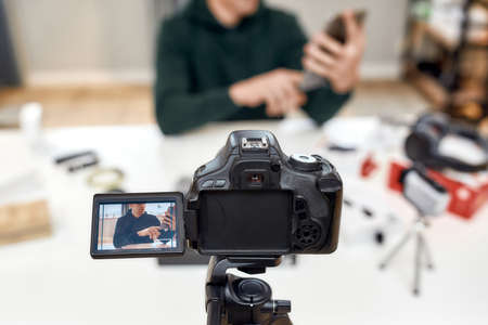 Close up of camera screen. Young male technology blogger recording video blog or vlog about new tablet pc and other gadgets at home studio. Blogging, Work from Home concept