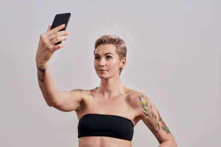 Selfie Time. Attractive tattooed woman with pierced nose and short hair taking a picture of herself, selfie using smartphone isolated over grey background