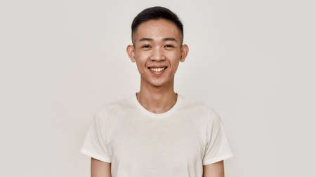Smile. Portrait of young asian man with clean shaven face smiling at camera isolated over white background. Beauty, skincare, health concept
