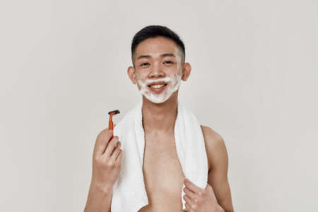 Morning routine. Portrait of shirtless young asian man with towel around his neck looking at camera while shaving his face isolated over white background. Beauty, skincare, morning routine concept