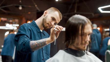 Young hipster guy getting new trendy haircut in the modern barbershop. Professional barber cutting long hair of client 写真素材