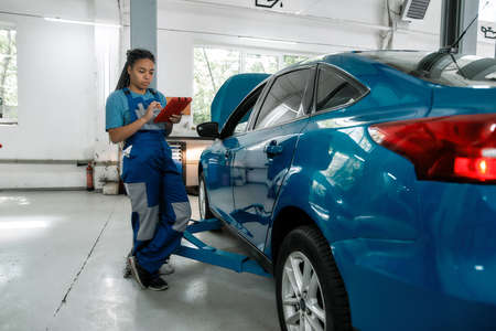 Meet the standard. Full length shot of african american woman, professional female mechanic using tablet pc, while standing near blue car with open hood at auto repair shop